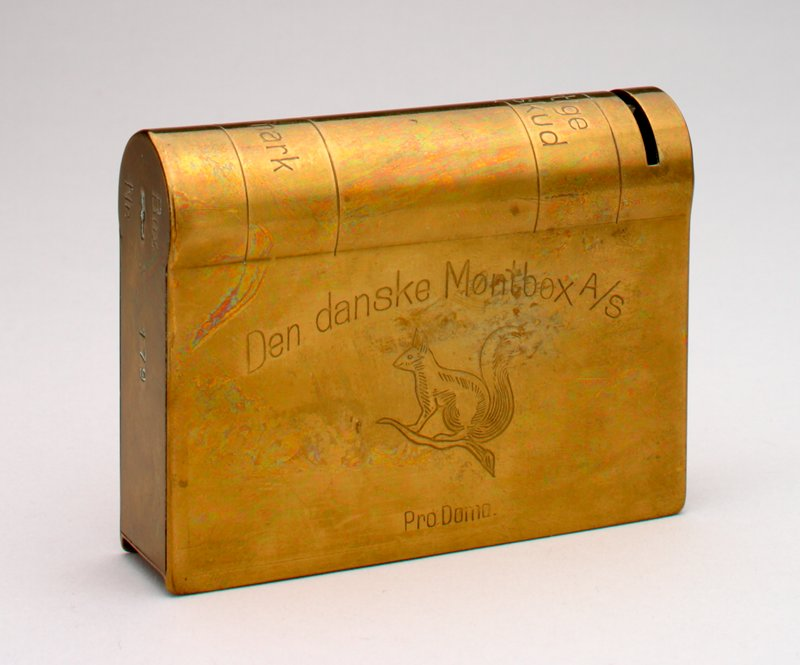 "book shaped brass bank with Danish words on spine, front and top: ""Den danske Mont box A/S""; picture of a squirrel engraved on front; King of Denmark's seal on top"