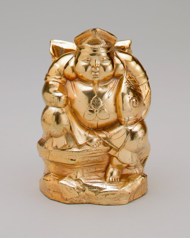 metal gold colored seated Asian figure; PR leg drawn up with arm resting on it; large fish under PL arm; pack on his back; leaf design on chest; he is barefoot