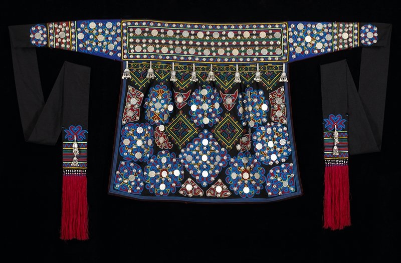 black and blue apron with many silver French coins and many silver knobby buttons attached; very long black apron ties with silver charms near the ends, colorful sleeve ends and reddish purple fringe on the ends; cross-stitch on top center panel; small beads