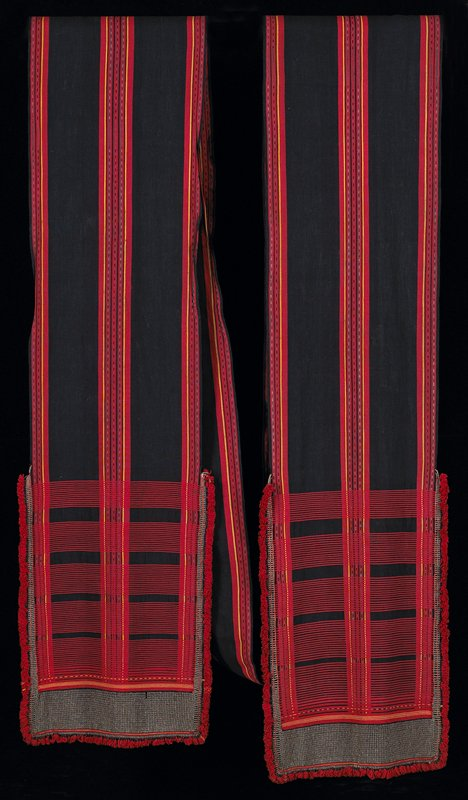 long strip of fabric with gray metal beads on ends; dark blue, red stripes, yellow stripes, lighter blue pattern; short red fringe on ends