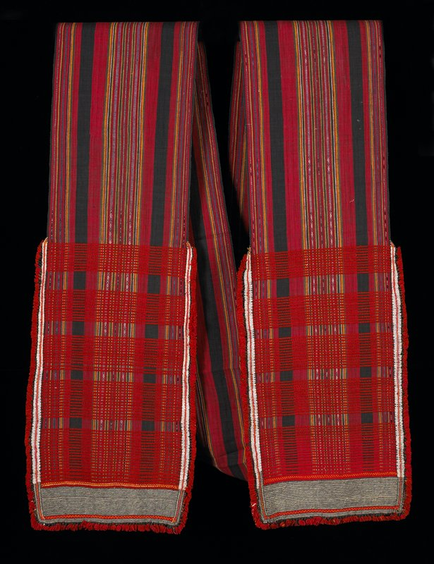 very long fabric strip; red, black, yellow, white, green and blue stripes; grey metal beads and white flass beads at ends; short red fringe; red embroidered strips at ends