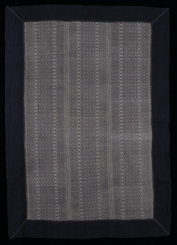 blue border with unfinished edges; three strips sewn together; white fabric with black star and geometric motif needlework