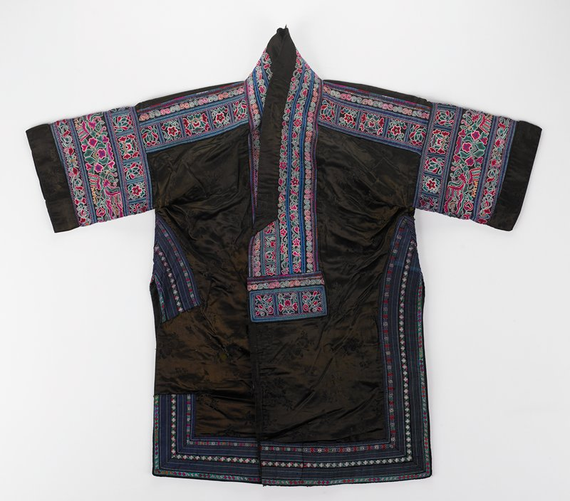 """brown silk damask with 7-1/2"""" longer front; open front with rows of blue, pink, green and white floral embroidery and applique on neck and front yoke, sleeves; side openings from under armhole have similar rows of embroidery with striped appliques which continue along hem in front and part way in back; woven ties with tassels and longer plain ties; black lining"""