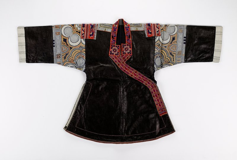 """unlined pounded indigo with batik inserts on upper sleeve and yoke and curled up back in circle patterns--blue, orange, white and gold; blue and white cuffs; jacket design has flared sides with vents and PL closure with ties; PL front short with inside ties; lower edges curved with applied tape bindings; applied embroidered shoulder bands and upper neck--floral patterns--blue, green and yellow on red; distinctive upper neck square closure; 2"""" woven band at front edges--similar colors"""