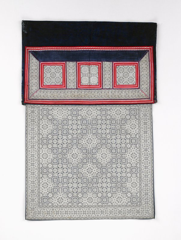 white, red, blue; tiny white cross stitch completely covers top square in a floral/geometric pattern with borders; lower rectangle the same but divided into three squares outlined in red and white narrow bands; blue at bottom and blue lining