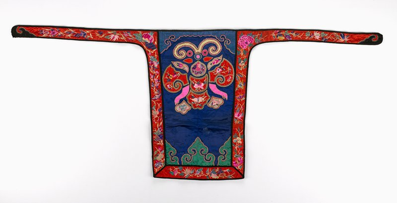 appliqued abstract embroidered figure on deep blue damask; red silk ties and border bound in black and embroidered in flora and fauna; appliques bordered with metallic thread; green, pink; black lining