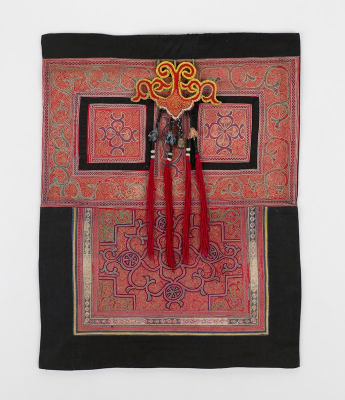 """top rectangle has black 2"""" band; embroidered section has two squares framed by embroidered vine-like pattern in chain stitch; squares have floral center; free-hanging padded medallion has four red tassels with beads and one brass bell; bottom rectangle has black border on three sides; center has elaborate Chinese design in red, purple, green; black lining"""