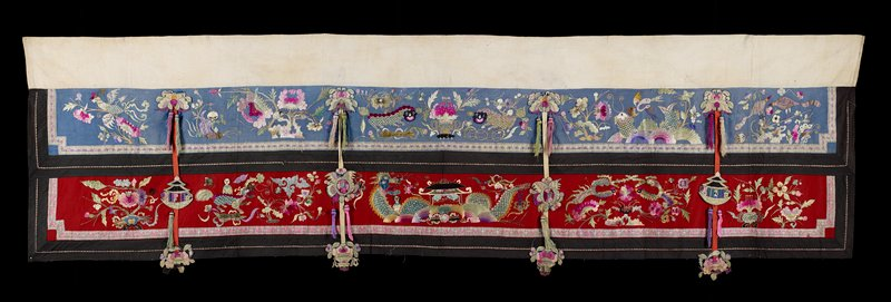 "two horizontal flannel sections, each with five embroidered tableaus depicting fanciful animated reptiles and animals separated by vertical straps with tacked-on floral and fauna appliqued medallions with tassels; top section is light blue, bottom red; brown border on each section; embroidery is multicolored pastels with black accents; doubled 8"" white strip across top, probably for hanging; dark blue lining"