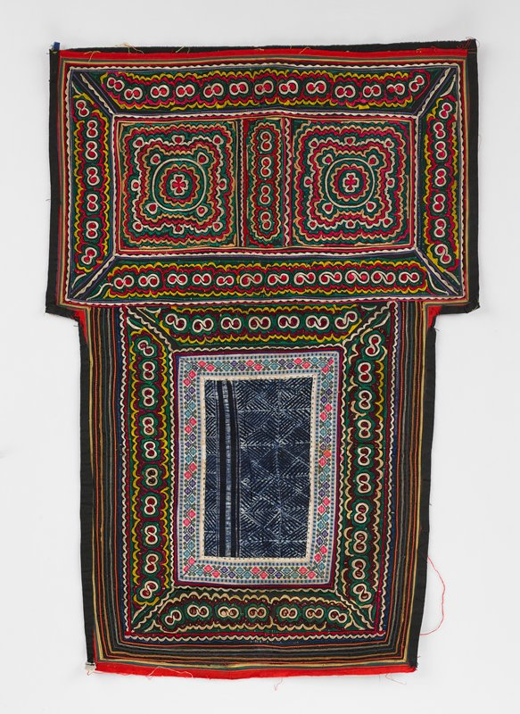 upper section has vertical rectangle of batik bordered in pink, blue and green braid; lower section has two squares of embroiderey over paper pattern in red, green, gold and white; both sections bordered on all four sides by same embroidery over paper
