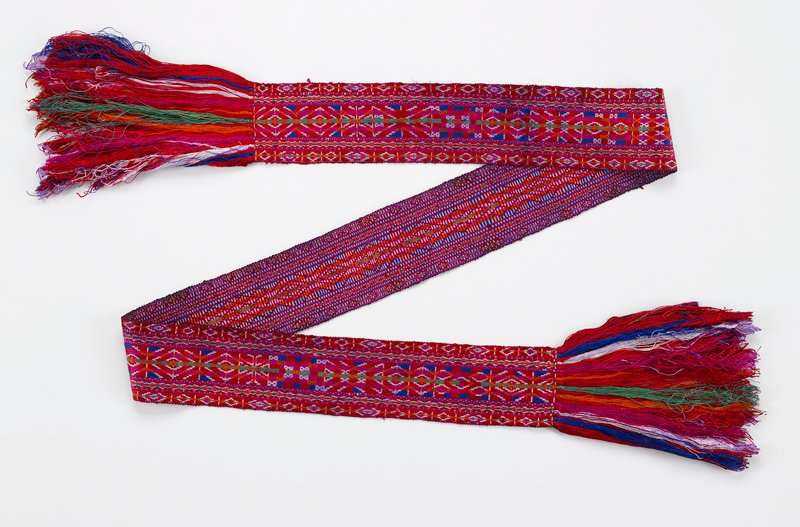 predominant center diamond patterns repeated in narrow borders; geometric embroidery in red, orange, green, magenta, blue, white fringe; self fringe with additional fringe added to each end