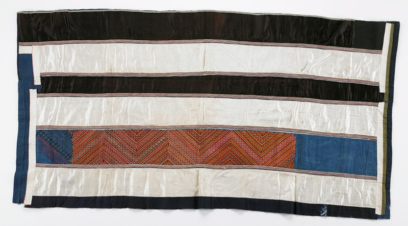 seven horizontal bands; # 2, 4, and 6 are white silk; #5 and 7 brown silk; #3 is zigzag embroidery with orange, green and blue; each band outlined in appliqued bands of narrow stripes; top waist band and lining are blue cotton