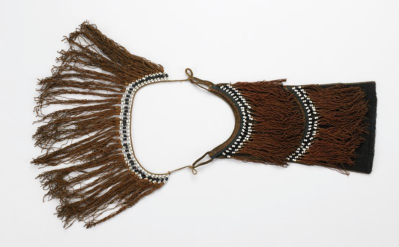 a) brown beaded fringe, brown/black and white beads hanging over brown/tan on black geometric embroidery; b) brown fringe with black/white beads attached to cord; (a) and (b) are tied together