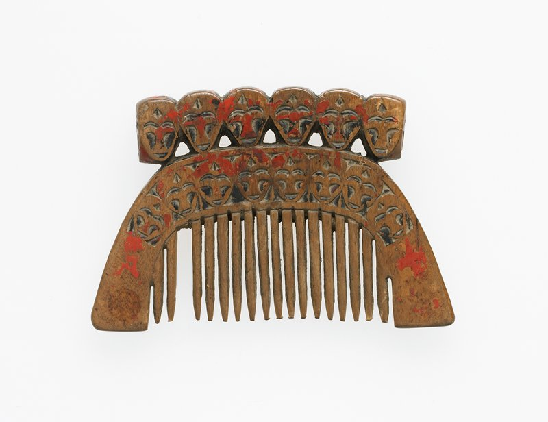 comb topped with row of five faces on each side; u-shaped area around teeth decorated with zigzags and diamonds