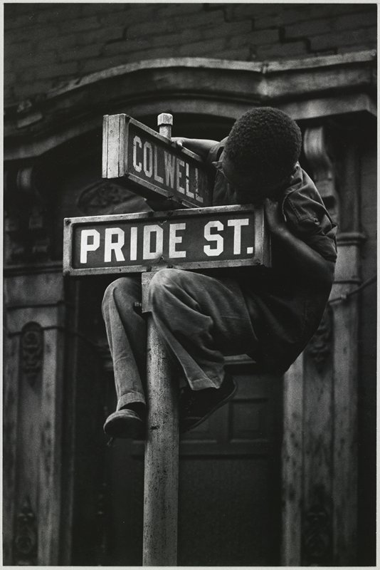 black boy hanging onto the top of a street sign; Pride St. and Colwell