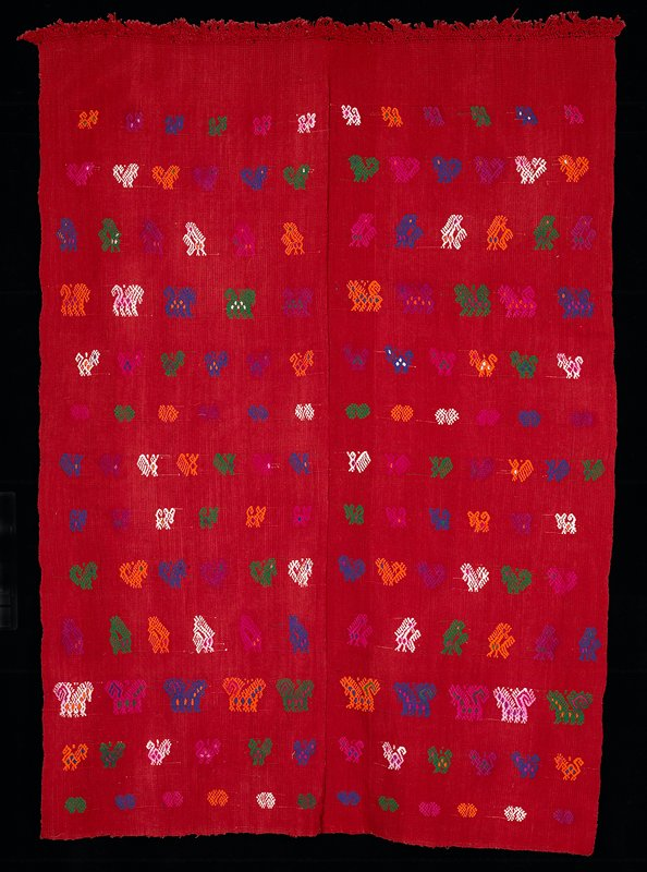 "two paneled red cotton tzute; woven on a back strap loom with zoomorphic brocaded figures in white, yellow, green, blue and magenta; one end of the tzute is finished with 1.5"" of macramé work fringes"