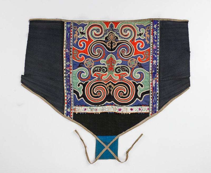"""red, green, blue silk applique; swirls and abstract motifs edged in raised white cotton tape; some edging yellow metal outlining; edged in tan tape that extends and crosses at bottom square (5x5""""); embroidered floral band on 3 sides; lined in blue cotton that extends beyond embroidered borders"""