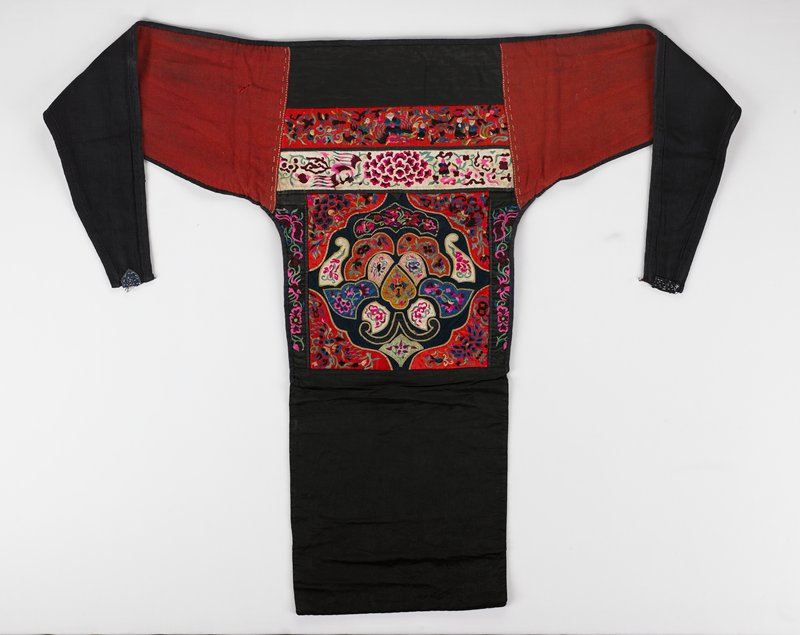red and white on black background fabric; multicolor satin stitch figures and floral patterns; large square with two wide bands above; red wool extensions edged and lined in indigo cotton; remnants of yellow metal-wrapped edging surround individual motifs; lined in indigo cotton; silk embroidery threads