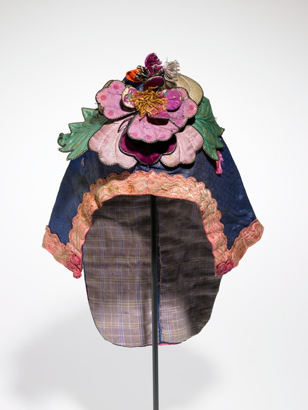 blue, purple, green, pink; covers neck and ears with flaps; three dimensional; wired, stiff flower petals on purple, tan, orange and blue; gold fringe in center; top has fringed butterfly with metal springs; blue background edged in pink braid; mauve plaid lining; PR knotted ball button; silver paper edges