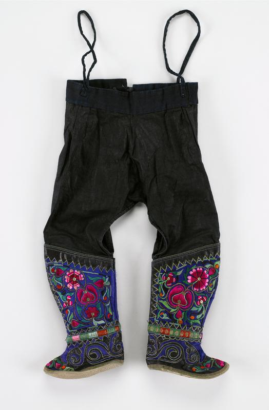 indigo pants with boots attached; black; heavily embroidered blue boots in stylistic floral and leaf patterns; some outlining in stitched metal; floral patterns in black, pink, green; lower boot is scroll applique (black) with pink flower toes; plain white soles; ties at waist