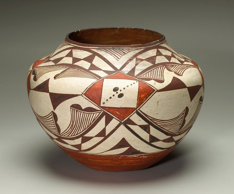 concave base; shoulder and neck decorated with geometric designs in dark orange and light and dark brown on cream; orange base