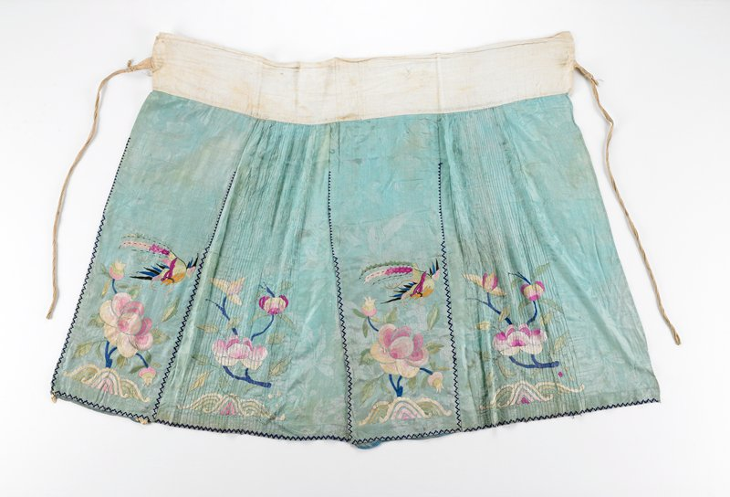 silk wrap skirt with wide cotton band at top and two ties; two partial lined panels of blue/green damask silk; large floral and bird patterns on lower half in shades of beige, rose, magenta, gold, green and blue; vertical embroidery on seams and edges; two parts of panels have finely tucked handstitched pleats the length of skirt