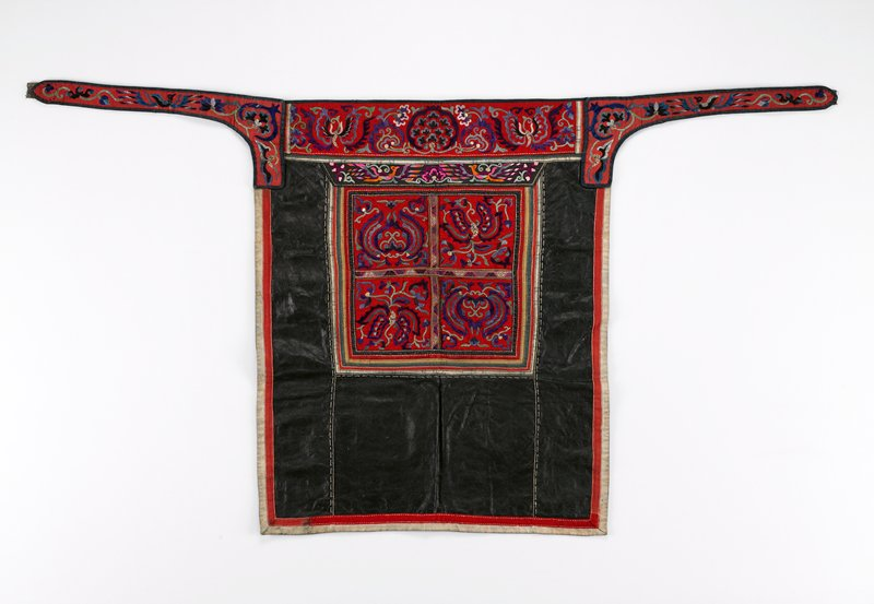 pounded indigo on three sides; top embroidery on red wool in purples, blues, greens, and white; attached straps embroidered on red cotton in similar colors; ties cut; center panel of red wool embriodered in similar colors; three sided striped border; three outside edges bordered in red wool and red and white cotton; top of center panel has different embroidered band on silk; open blue lining