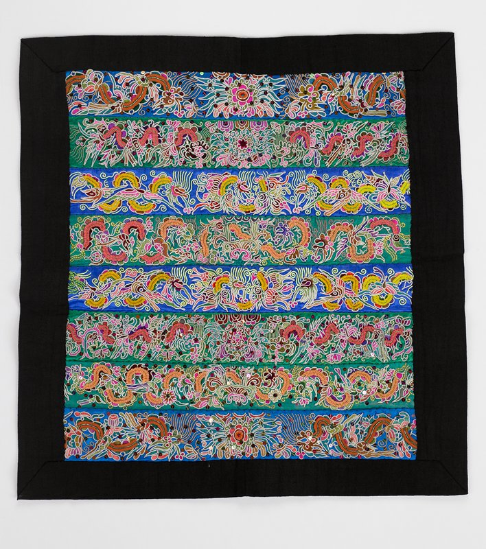 eight elaborately embroidered horozontal bands, bright multicolored embroidery on bright blue or green backgrounds; lined in black cotton which makes mitered border in front