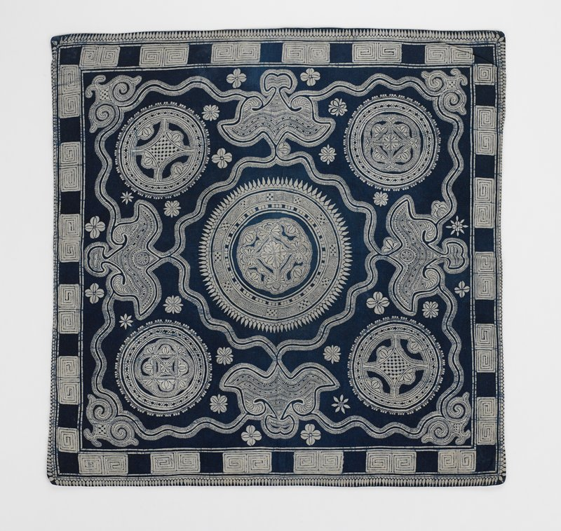 grey lined indigo batik on grey background; large center circle with geometric design; four smaller corner circles; running ribbon band conects design throughout; outside geometric border
