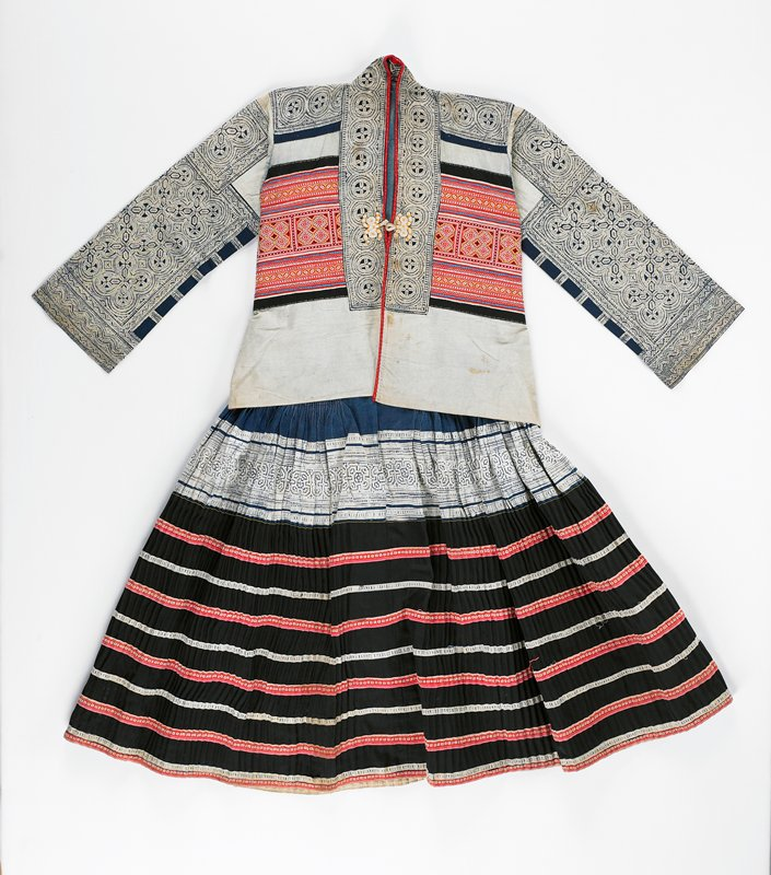 blue lined back with black side edging; front--applied batik neck band; edged in red; orange and white frog closures; center fronts have heavy cross stitch embroidery on applied red background; wide lower beige area--plain; shoulders and sleeves have applied batik in circle patterns; back--upper circles in square pattern batik; long lower back heavily embroidered--yellow, red, black--separated by applied horizontal bands; front is vented and tapered