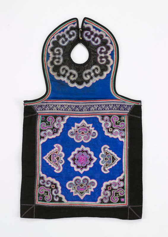 neck piece has two brass button fasteners; scrolled applique on pounded indigo on blue silk, edged in red, green and white; bottom blue silk square bordered in black with nine irregularly shaped appliques and embroiderey, with sequins; black indigo lining