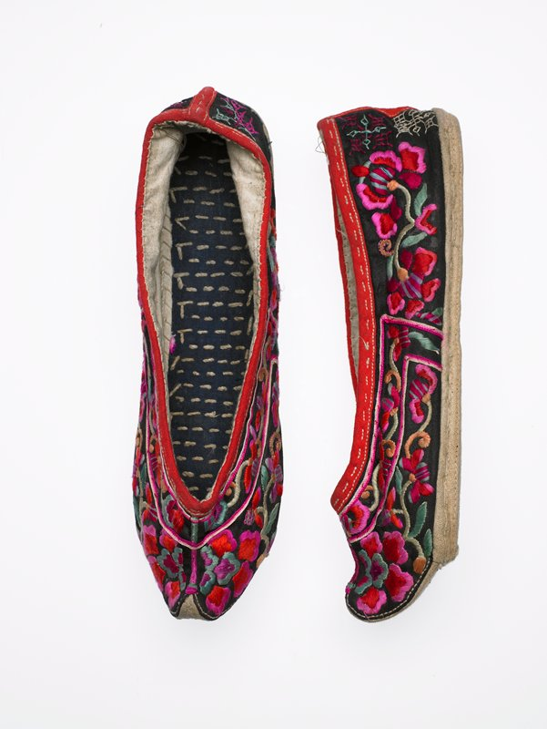 upturned toe; floral embroidery in red, pink and green throughout on black; red binding at opening; firm, stiff stitch beige sole; white lining