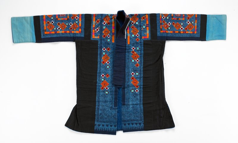 black background with geometric blue batik inlays, turquoise cuffs; orange, turquoise, brown applique and silk embroidery on front back and sleeves; blue cotton lining throughout; side slits