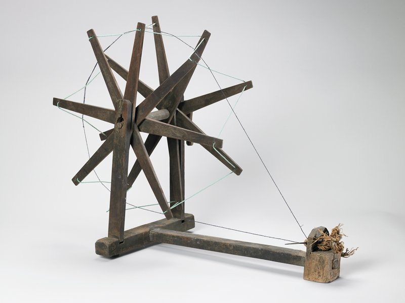 two-sided open wheel with eight spokes on each side; green yarn threaded in zigzag through holes in ends of spokes; T-shaped base; twined rope and needle-like piece at small end of T