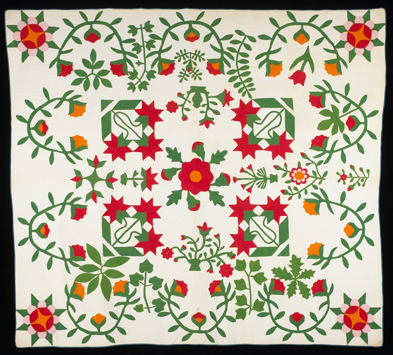 orange, red, and red and white print flowers of varying styles; central red and orange floral medallion; white ground and backing