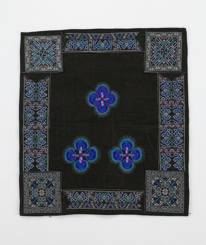 black; four cross stitched side borders and corner squares in blue, pink, green; center has three brilliant designs of crosses and circles of blue with green feathering. Surface ornamentation