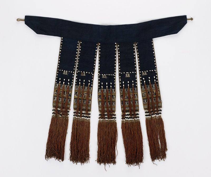 four strips of blue fabric attached to blue waistband; white knot closure; strips decorated with geometric and foliate embroidery, black and white beads and brown tassels
