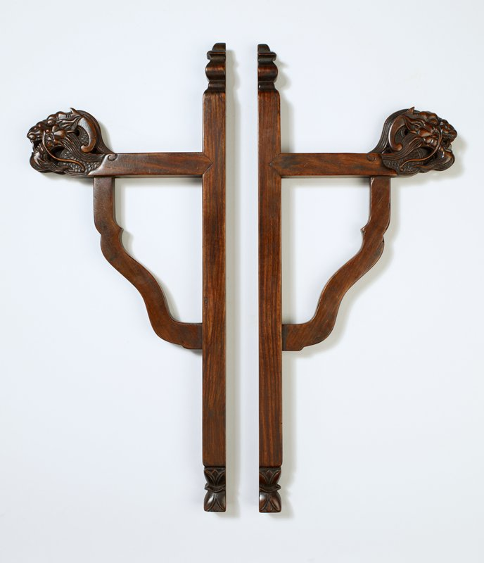 wall bracket; decorative spindle at top, lotus blosson at bottom; section that extends from wall terminates in dragon's head with open mouth