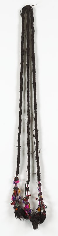 "brown wool; three thick rolled strands, echa ending in two thin decorative beaded and tasseled multicolor strands; attached at ""top""; tape piece at top says ""1168"""