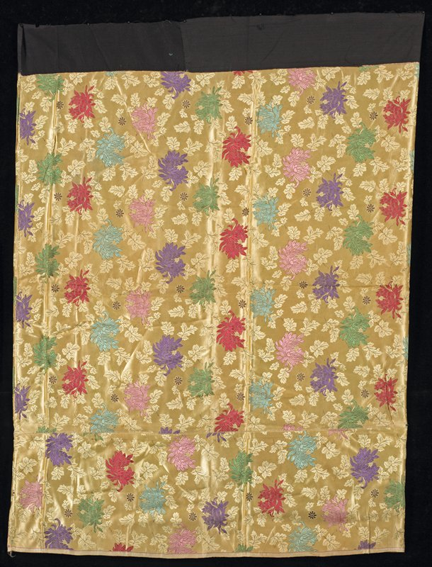 """woven overall crysanthemum pattern on tan field in pink, red, green, purple, aqua; 9 1/2"""" addition on bottom; black cotton waistband"""