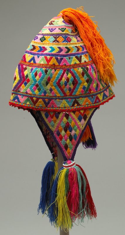 finely knit; brightly colored with tassels at neck and top; multicolored; design is circular pattern of various sizes and geometric shapes