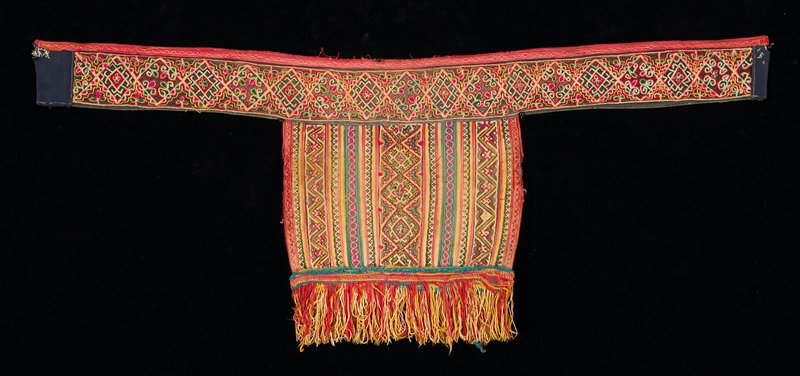 vertical rows of applique and embroidery in geometric patterns in yellow, orange, pink and green; fringe on bottom is very thin, woven; band has continuous diamond embroidery; lined in blue