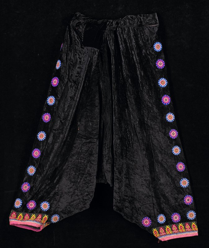 black rayon velvet; circle embroidered appliques on both sides and around bottom of leg; cross stitch embroidered design at edges of legs; elastic band in waist; blue, pink, yellow