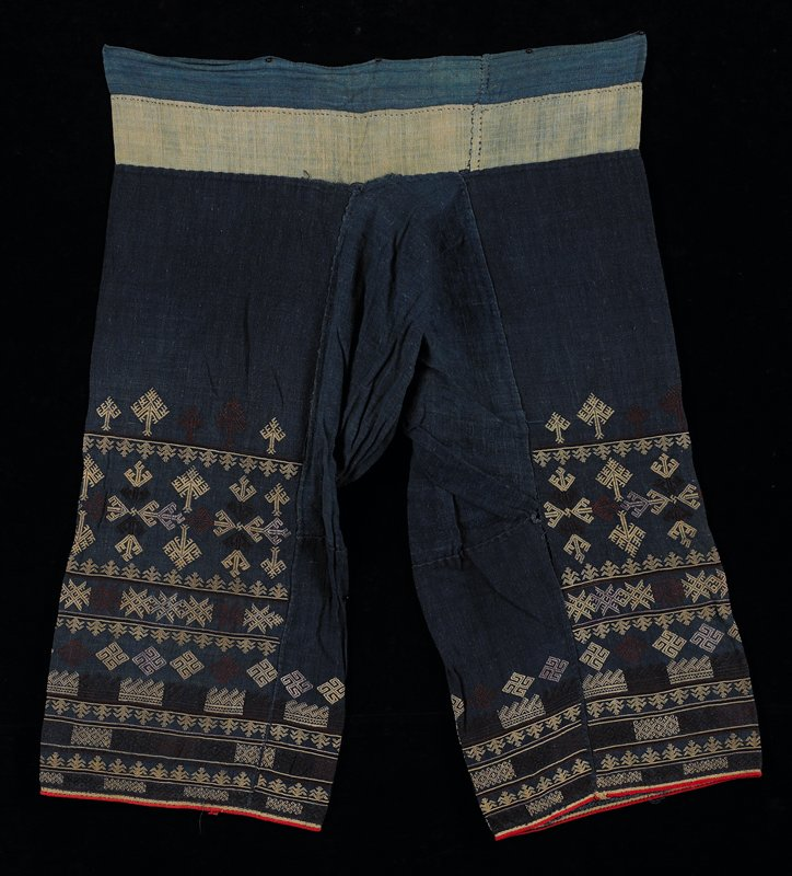 blue with geometric embroidery covering about half of leg area; crotch gusset; tan and light blue waistband; embroidery is tan and burgundy; red piping on leg bottoms