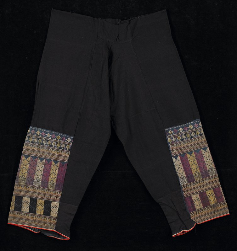 blue/black cotton with most of legs covered in geometric embroidery in muted purple and yellow; red piping on cuffs; gusset