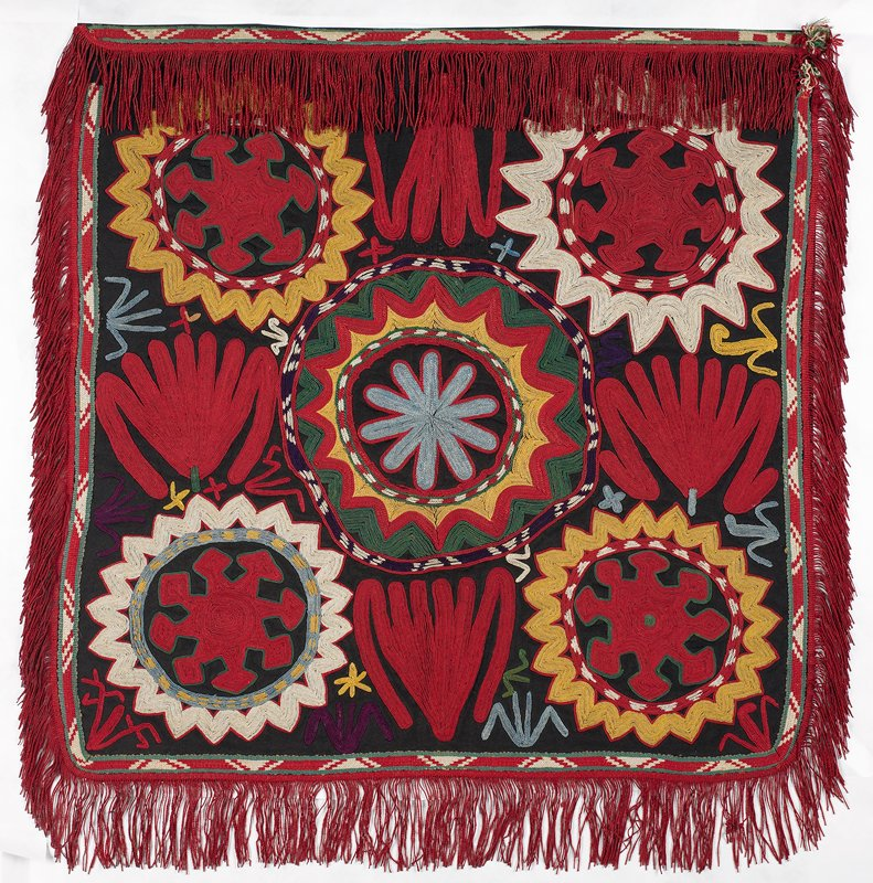 Fringe with warp-twined (LM) heading, warp-twined (LM) band Black wool ground with silk chain stitch embroidery and two attached silk edgings on four sides. The fringe is cotton. Interior edging is woven in red and white. Outside is all red and carries the fringe. The embroidery is presently hand stitched to a fabric mount; the verso is not visible. It is mounted and sewn through a white flannel on a black wool covered strainer. Red and yellow dominate.