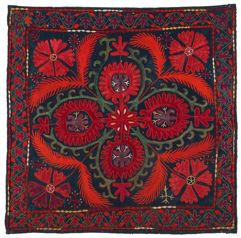 """No backing cloth. Hand jwoven indigo-dyed pieced wool ground with polychrome wool and silk embroidery. There is no finishing treatment on the edges. Red dominates. Large center square pattern with 2 1/2"""" - 3"""" border all sides."""