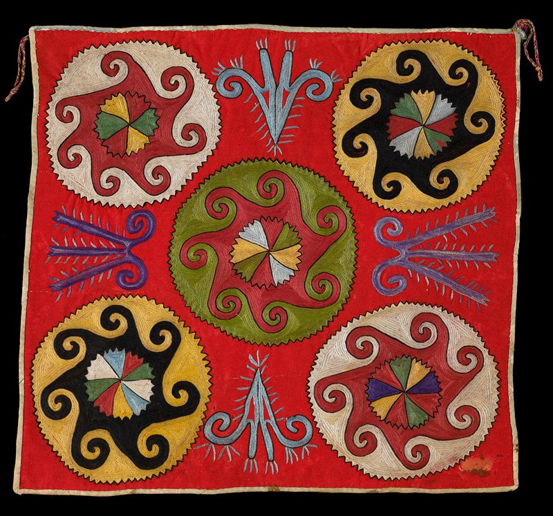 Printed cloth band. Red wool ground with polychrome silk embroidery and printed cotton twill binding. The gringe has been removed since photography by donor. The embroidery is worked through a substrate of printed cotton fabric. There is no backing.