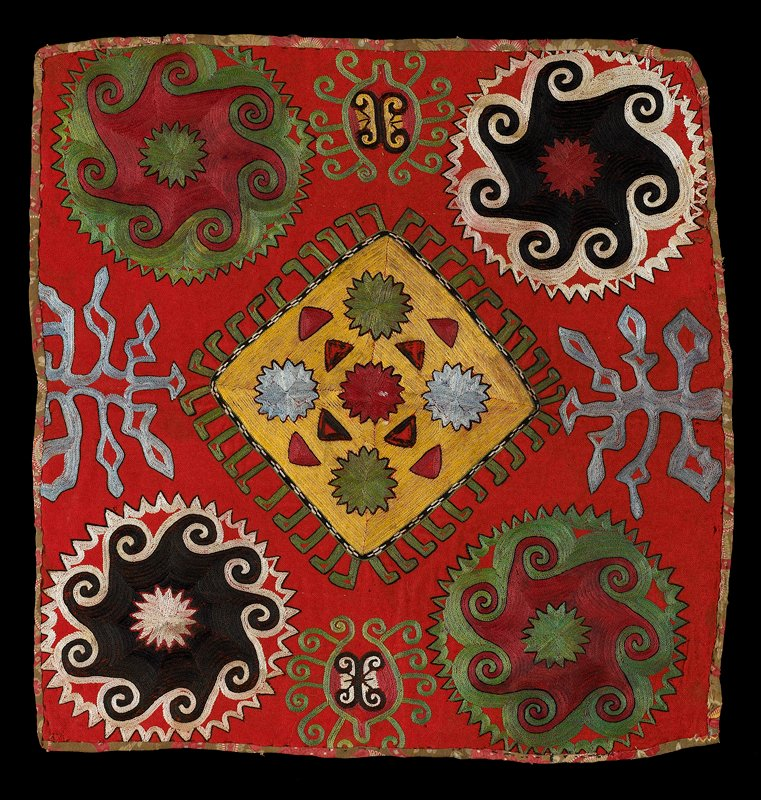Pieced, printed lining (also forms edge finish). Red wool ground with polychrome silk and synthetic embroidery. The printed cotton backing is turned to the front along the edges to form a self-binding. Chain stitch outlining with back stitch fill.