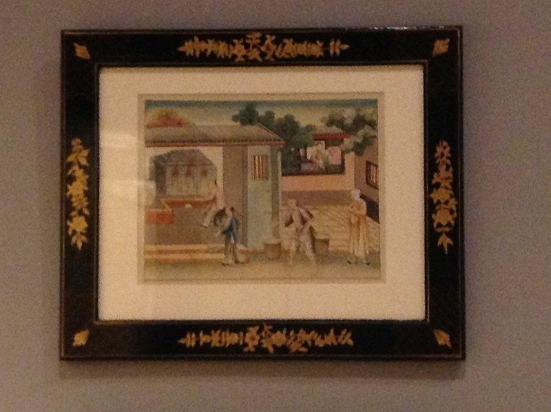 woman with child at window, URC; man in yellow tunic, LRC; man with yoke follows another figure carrying a small basket; seated man stokes a firing kiln; black, gold and red lacquer frame