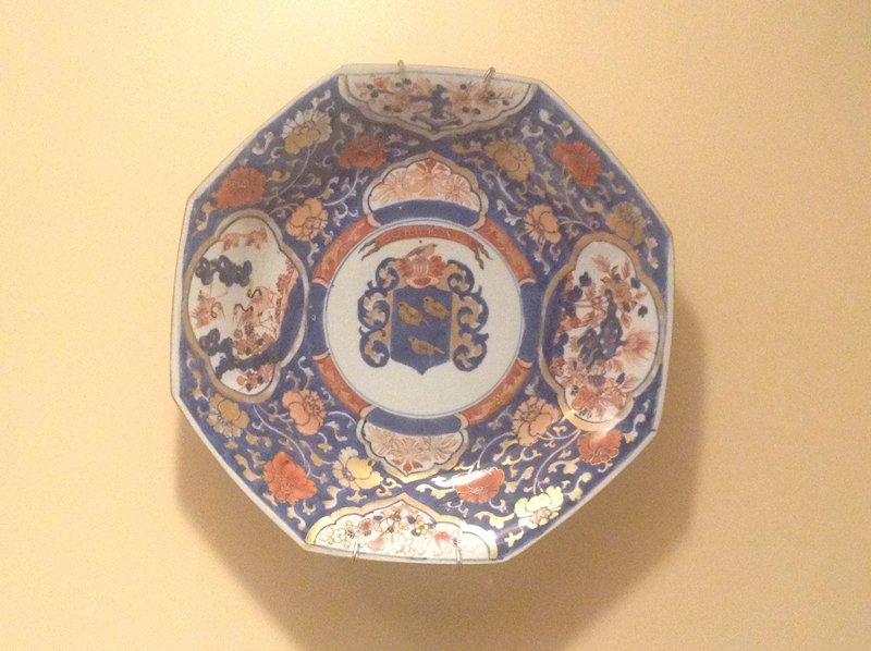 "octagonal; Imari decorated with central rondel depicting coat of arms below scroll inscribed, ""CORBEAU"", surrounded by shaped panels enclosing plants, a lion and a group of cranes; washed-blue ground with camilla sprays"
